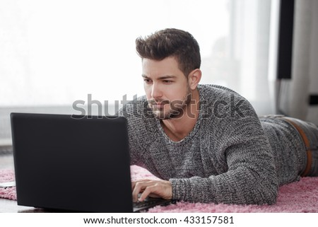 Caucasian man using laptop while lying on floor at home