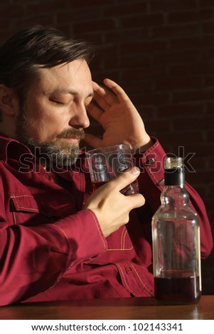 Caucasian man with a nice bottle sitting on a dark background - stock photo