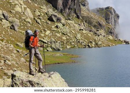 Caucasian man with backpack rests near mountainous lake in Caucasus, Georgia - stock photo