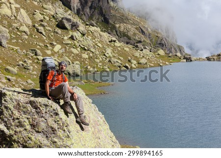 Caucasian man with backpack rests near mountainous lake in Caucasus, Georgia