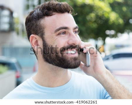 Caucasian man with beard at phone outdoor in city