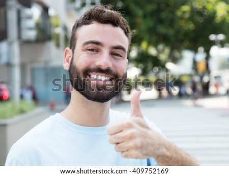 Caucasian man with beard showing thumb outdoor in city - stock photo