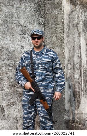 Caucasian man with black sunglasses in urban warfare holding rifle - stock photo
