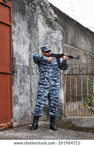 Caucasian man with black sunglasses in urban warfare holding rifle near gate - stock photo