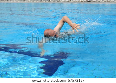 Caucasian man with glasses swimming in pool