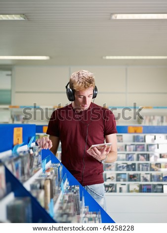 caucasian man with headphones, choosing cd in music shop. Vertical shape, front view, waist up, copy space - stock photo