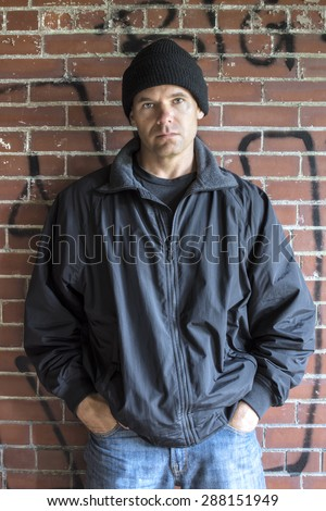 Caucasian man with serious expression wears hoodie, jacket and jeans and leans against brick wall with graffiti in urban setting with hands in pockets - stock photo