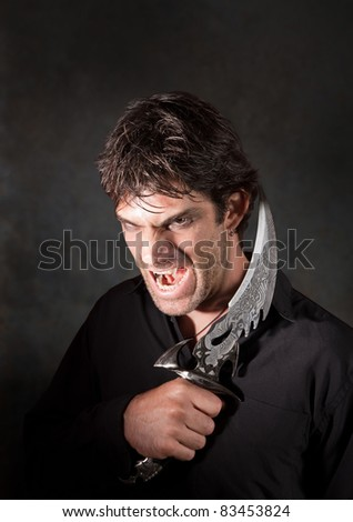 Caucasian man with sharp knife yells over maroon background - stock photo