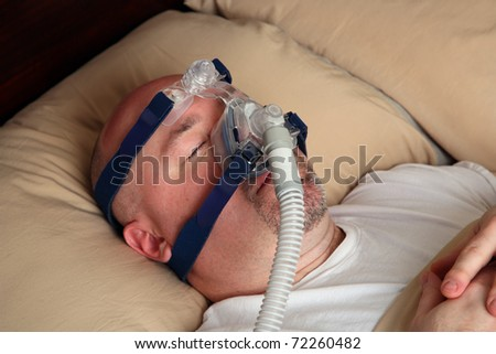 Caucasian man with sleep apnea using a CPAP machine in bed. - stock photo
