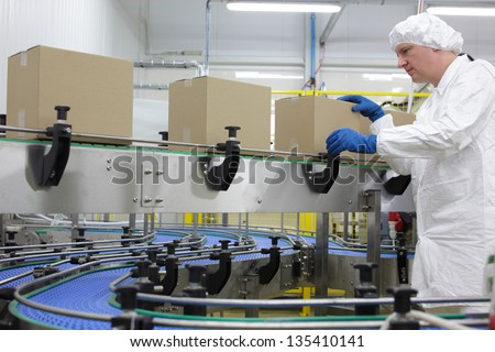 caucasian man worker in white apron, cap and blue gloves at  packing line in factory - stock photo