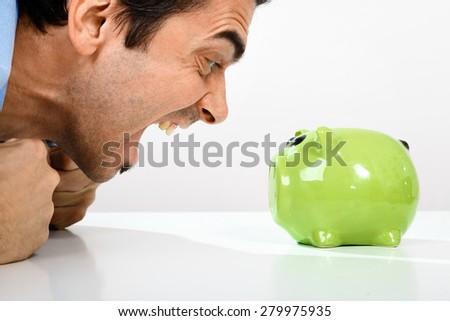 Caucasian man yelling at green piggy bank - stock photo