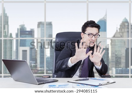 Caucasian manager with afraid expression try to hold something with his hands in the office