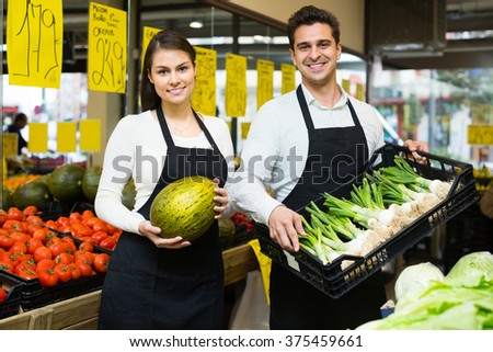 caucasian market workers with assortment of apples, prices on Spanish - stock photo