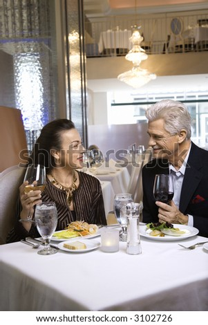 Caucasian mature adult male and prime adult female sitting at restaurant table. - stock photo