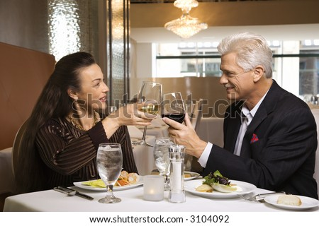 Caucasian mature adult male and prime adult female sitting at restaurant table toasting wine glasses. - stock photo