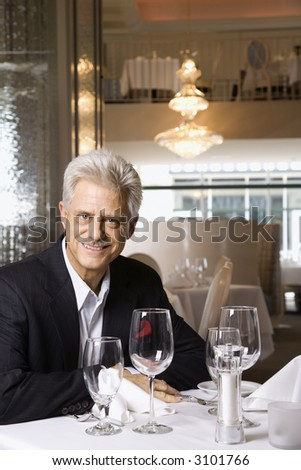 Caucasian mature adult male sitting at restaurant table looking at viewer smiling.