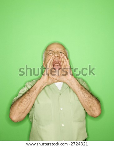 Caucasian mature adult male with hands to mouth yelling. - stock photo
