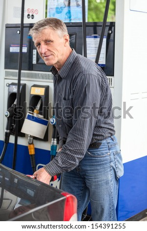 Caucasian mature man refueling car with gasoline