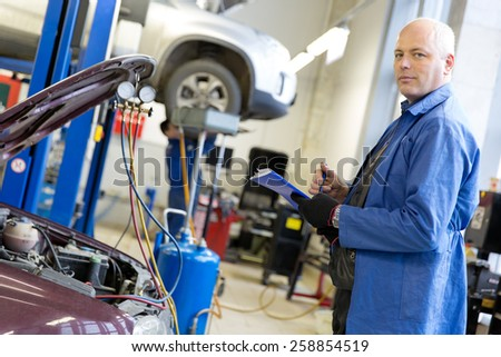 Caucasian mechanic engineer with notebook during car air conditioner refilling on automobile service station background - stock photo