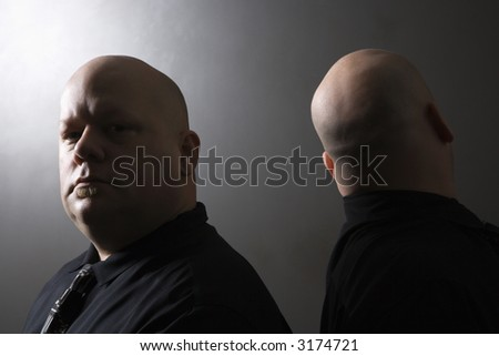 Caucasian mid adult bald identical twin men standing back to back and looking at viewer. - stock photo