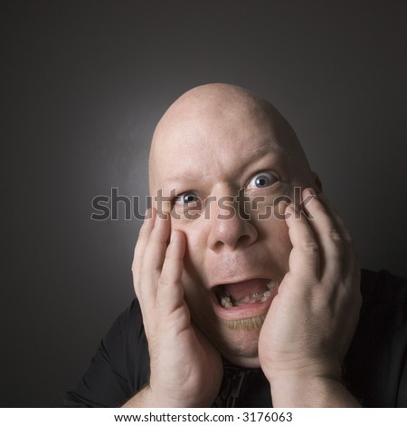Caucasian mid adult bald man with hands to face making scared facial expression. - stock photo