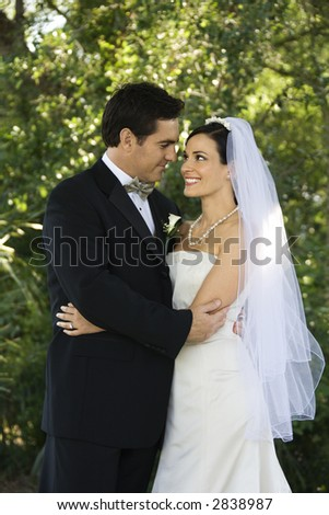 Caucasian mid-adult bride and groom embracing, smiling and looking at each other.