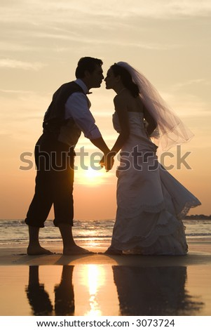 Caucasian mid-adult bride and groom holding hands and kissing barefoot on beach at sunset. - stock photo