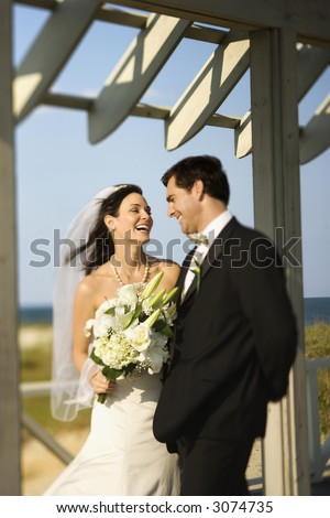 Caucasian mid-adult bride and groom looking at each other talking and laughing.