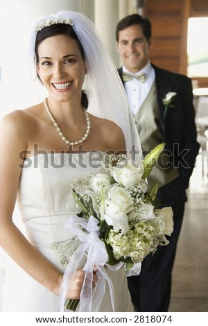 Caucasian mid-adult bride and groom standing on porch looking at viewer and smiling. - stock photo