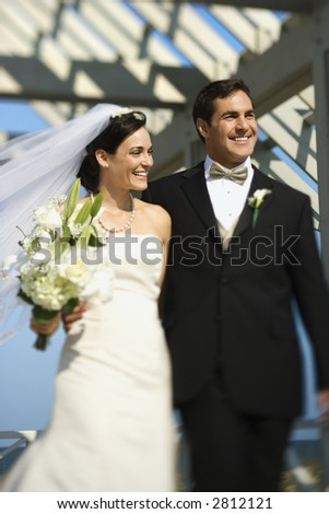 Caucasian mid-adult bride and groom walking together smiling.