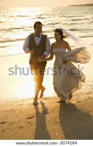 Caucasian mid-adult bride and mid-adult groom holding hands running barefoot on beach. - stock photo