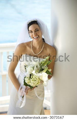 Caucasian mid-adult bride holding bouquet laughing.