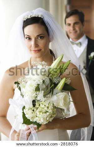 Caucasian mid-adult bride holding bouquet with groom in background.