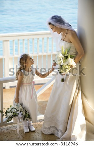 Caucasian mid-adult bride holding hands with flower girl.