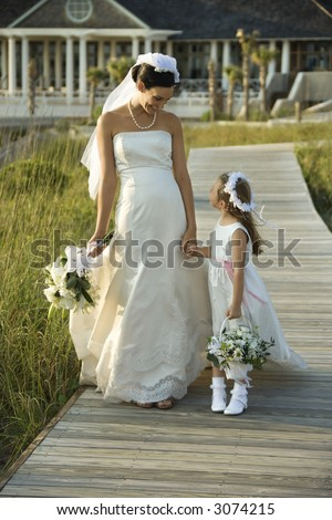 Caucasian mid-adult bride holding hands with flower girl walking down wooden beach walkway.