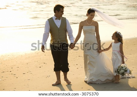 Caucasian mid-adult bride, mid-adult groom and flower girl holding hands walking barefoot on beach. - stock photo