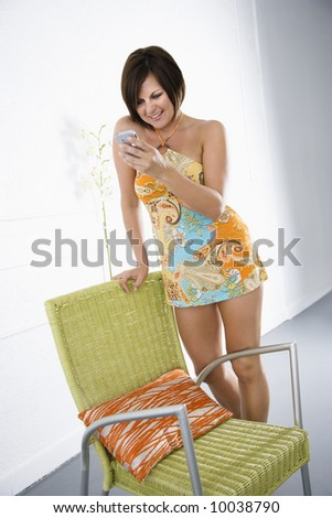 Caucasian mid adult brunette woman looking at PDA and smiling.