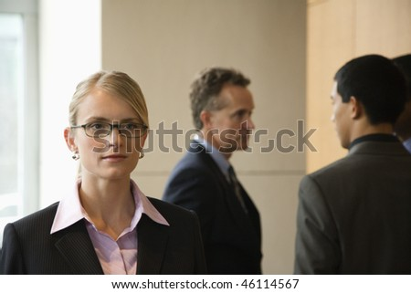 Caucasian mid-adult business woman in foreground with group of businessmen in the background. Horizontal format. - stock photo