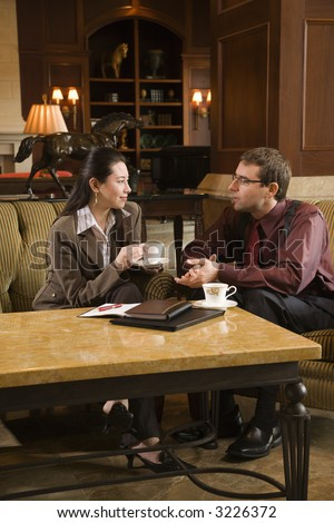 Caucasian mid adult businessman and woman drinking coffee and conversing. - stock photo