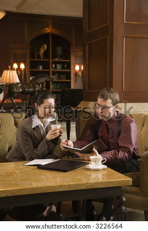 Caucasian mid adult businessman and woman drinking coffee and looking at  portfolio. - stock photo