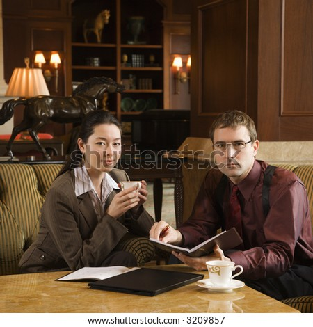 Caucasian mid adult businessman and woman drinking coffee and looking at viewer. - stock photo