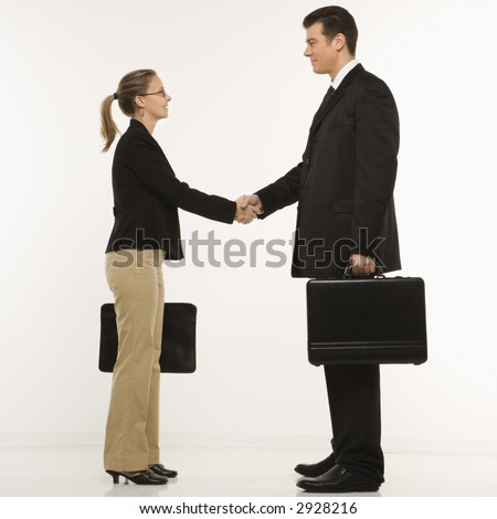 Caucasian mid-adult businessman and woman shaking hands and holding briefcases. - stock photo