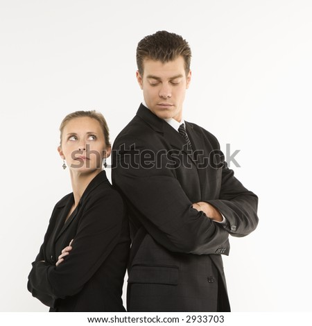 Caucasian mid-adult businessman and woman standing back to back looking at each other. - stock photo