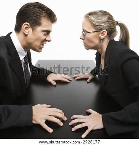 Caucasian mid-adult businessman and woman staring at each other with hostile expression. - stock photo