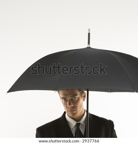 Caucasian mid-adult businessman  looking out at viewer from under umbrella. - stock photo