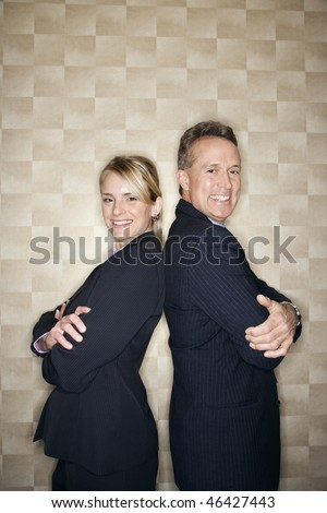 Caucasian mid-adult businesswoman and middle-aged businessman standing back to back and smiling at the camera. Vertical format. - stock photo