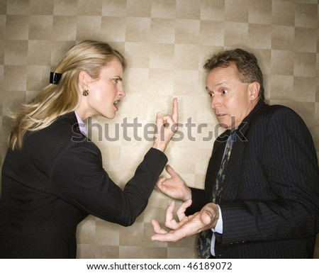 Caucasian mid-adult businesswoman angrily giving middle finger to middle-aged businessman who shrugs at her. Horizontal format. - stock photo