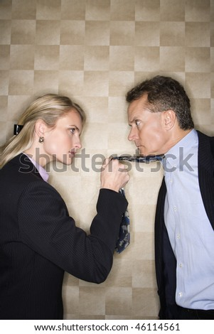 Caucasian mid-adult businesswoman staring into eyes of a middle-aged businessman while pulling angrily on his tie. Vertical format. - stock photo