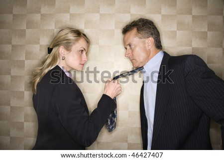 Caucasian mid-adult businesswoman staring into eyes of a middle-aged businessman while pulling on his tie. Horizontal format. - stock photo