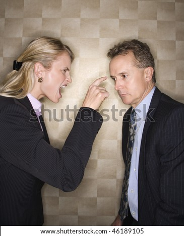 Caucasian mid-adult businesswoman yelling and pointing at middle-aged businessman. Vertical format. - stock photo